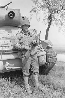 PFC Weslyn R. Sucher, 83rd Armored Reconnaissance Battalion, 3rd Armored Division, rests against an M8 Howitzer Motor Carriage at Dessau, Germany.