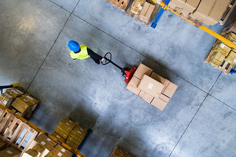 Male warehouse worker pulling a pallet t