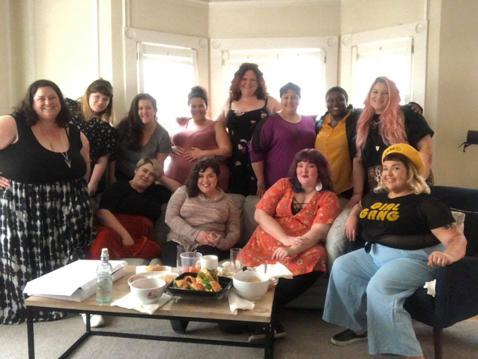 A group of plus size women of many difference shapes, ethnicities, and sizes from 16 to 30+ come together for a picture in a living room. Laurel Dickman, Emily Casey, and Mama Fierce's Briana Hernandez are seated in front. Photo by Jen Rees.