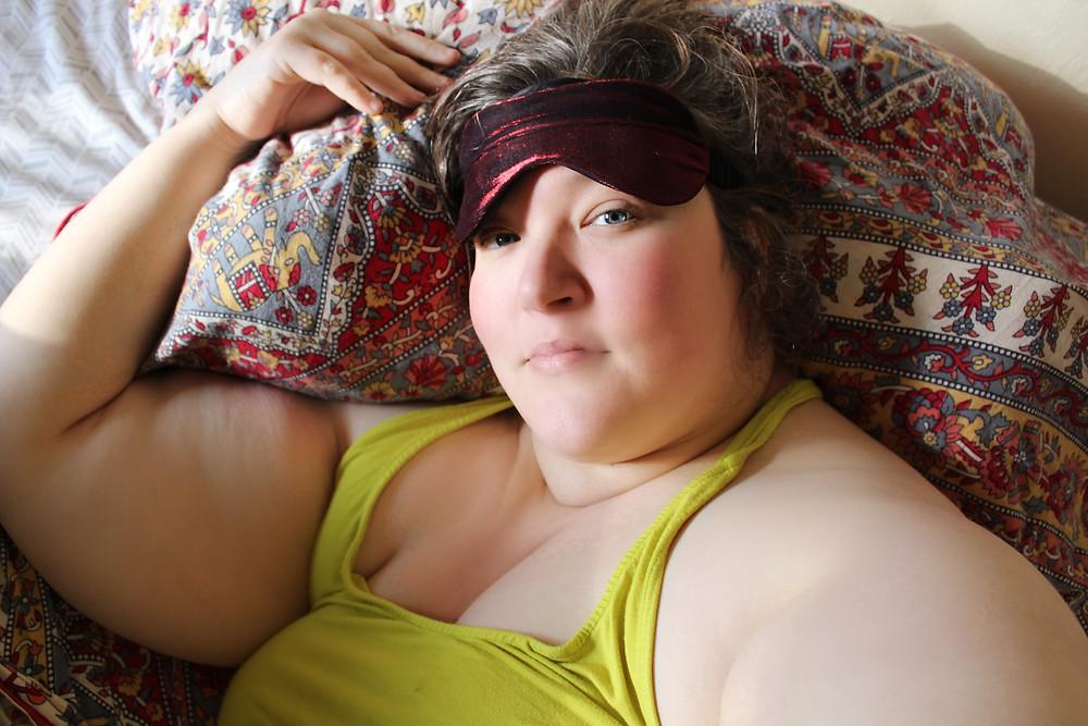 Laurel Dickman lays in repose, modeling the red metallic silk eye mask by TITOV.