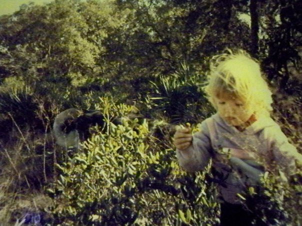 Author as a two or three year old, circa 1986 or 87. Little blonde girl looks down wistfully while playing in the Florida brush with large German Shepherd in the background.