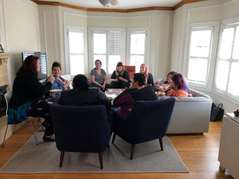 A group of plus-size women sit around in a circle. Naomi Finkelstein of The Body Positive leads a discussion as the group listens. Photo by Jen Rees.
