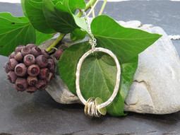 Large hammered wire oval pendant with silver and brass discs and links on long chain