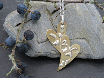 Overlapping brass hearts with fused silver on long chain