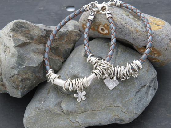 Silver/grey leather bracelets with mixture of links, cuffs and charms