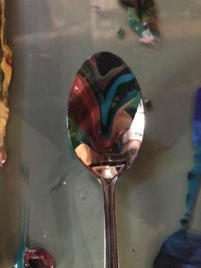Scraped paint swirls on a spoon