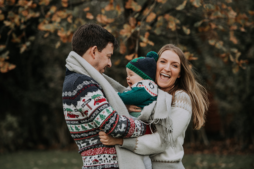 Christmas outdoor family portrait of Mum, dad and Baby Boy smiling