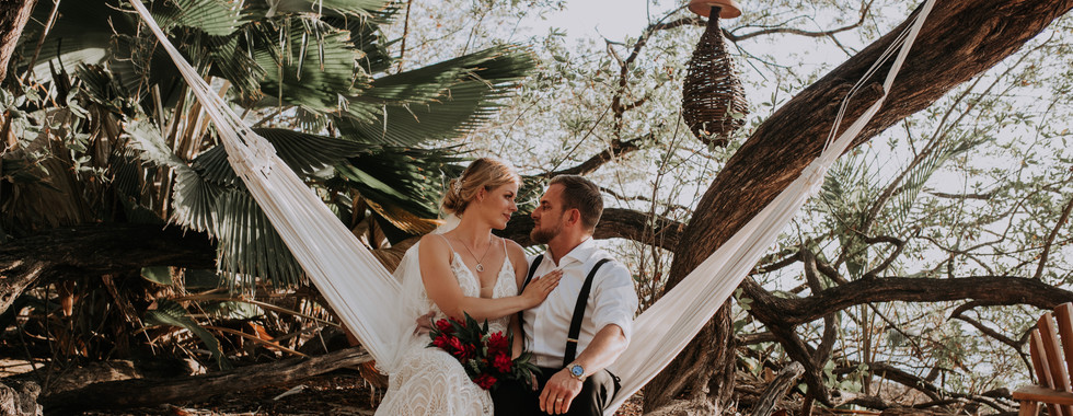 Bride and Groom Sitting in a white hammock on the beach in Costa Rica