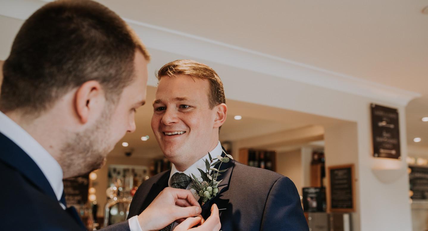 groomsmen putting on button hole