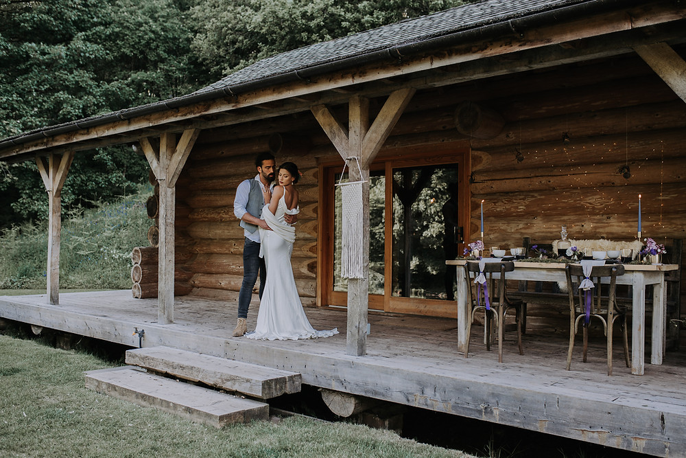 Bride and Groom standing at log cabin on wedding day cumrbia