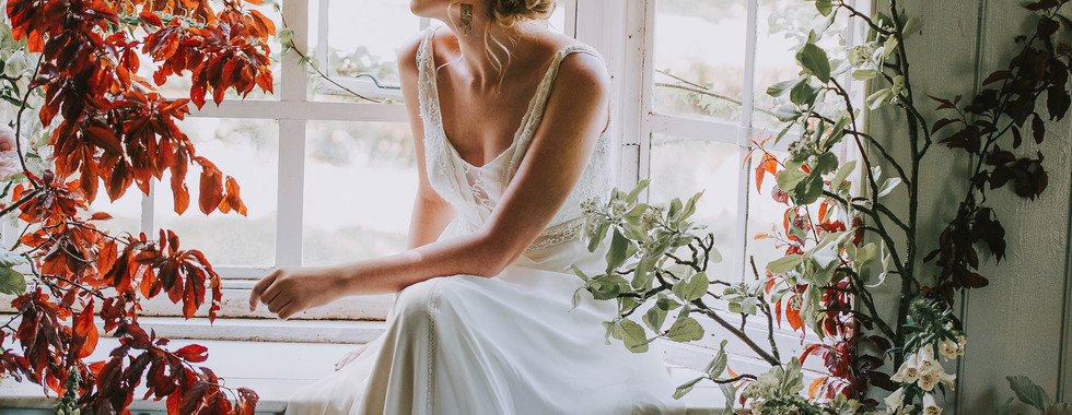Bride sitting at window in boat house with flowers and candels