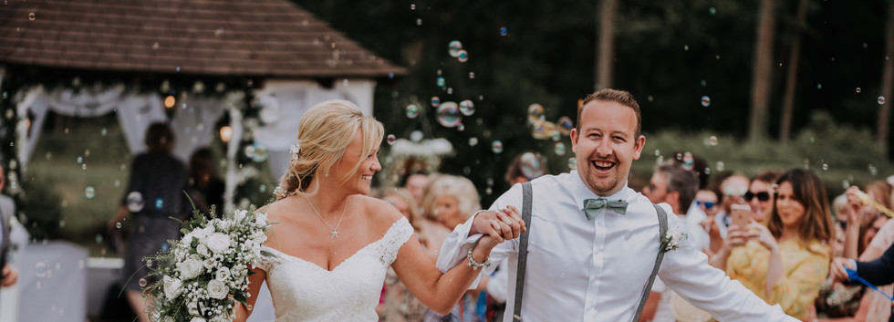 bride and groom with bubbles at ceremony in surrey