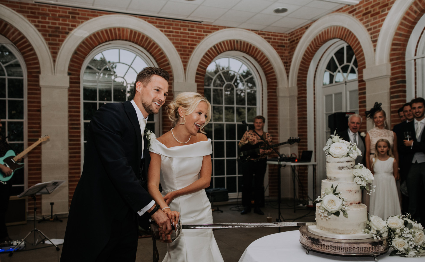 bride and groom cut cake with sword at Great Fosters