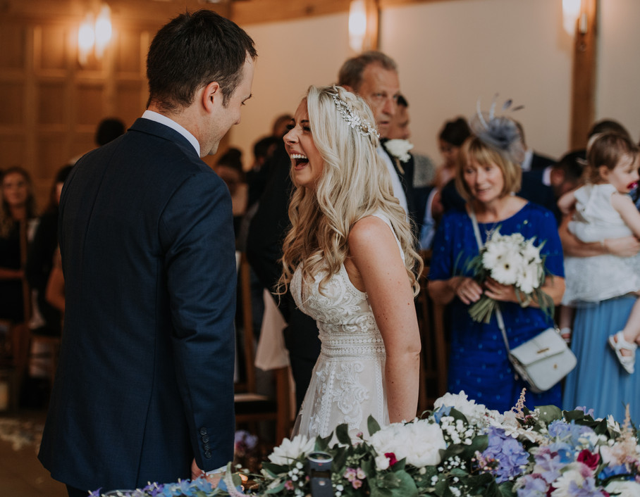 Laughing bride at wedding ceremony at riverdale Barn