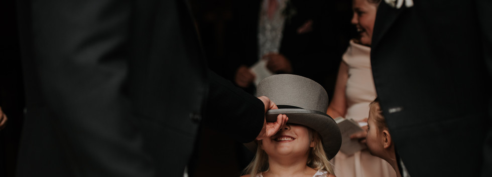Little girl wearing top hat at wedding