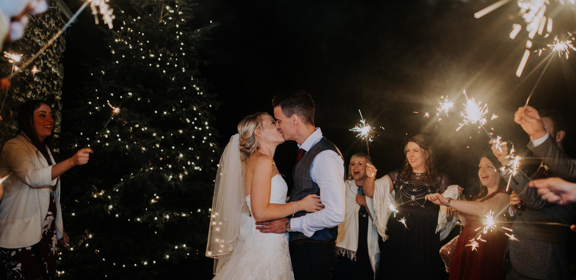 bride and groom kiss with sparklers