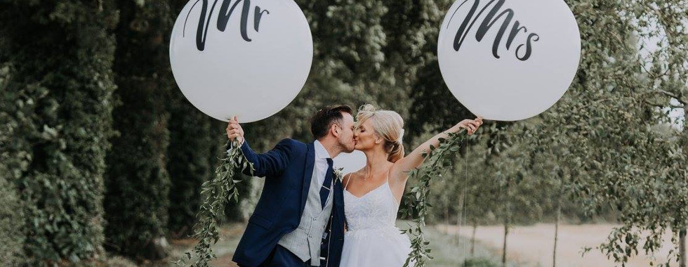 Bride and Groom Kissing holding Mr and Mrs balloons