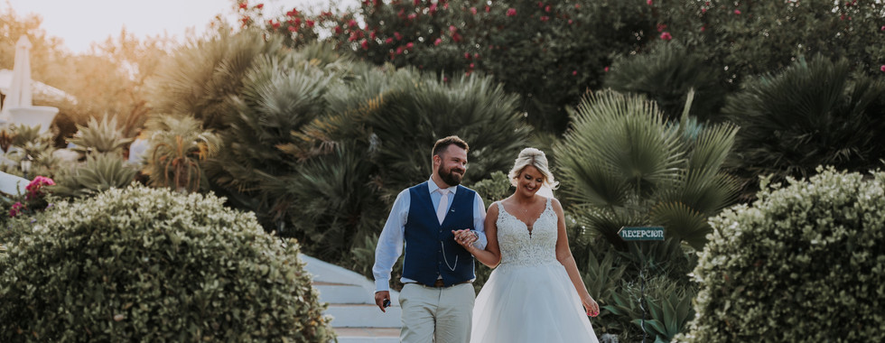 Bride and Groom Walking through orchard at Destination Wedding in Spain