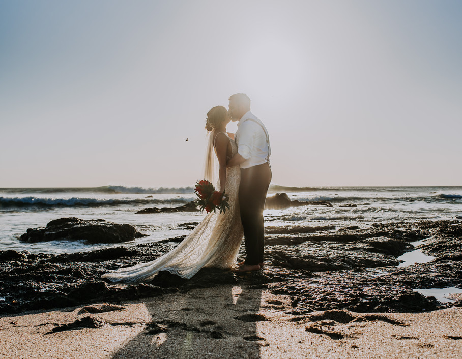 Bride and Groom kissing on the beach at sunset