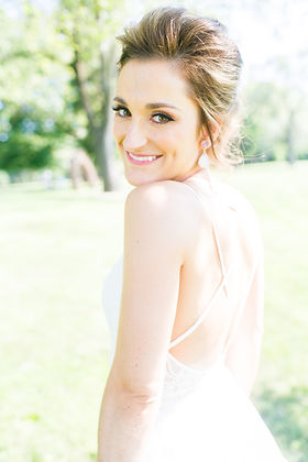 A bride sweetly smiling over her shoulder to the camera with her hair and makeup styled.