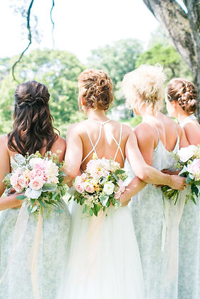 A bride with her bridesmads outside showing their backs to the camera and their hair styled holding flowers.