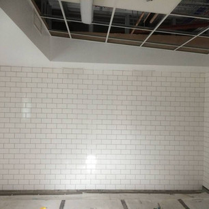 Floor to ceiling white tiles with grey grout