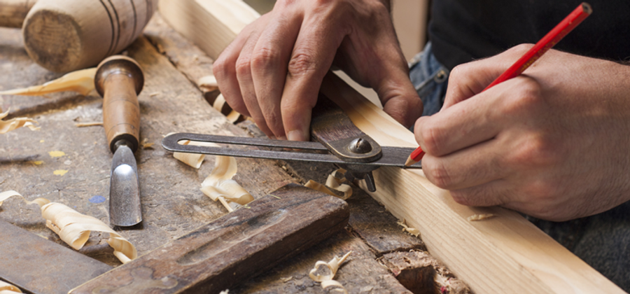 Carpenter drawing measurements on wood