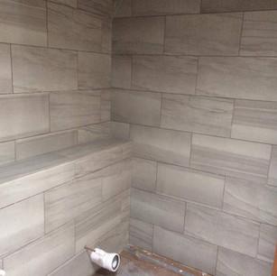 Grey tiles, floor to ceiling, in bathroom