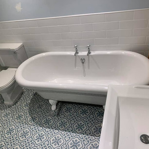 White wall tiles behind bath and geo grey tiles on floor