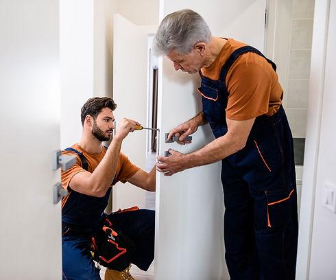 Handymen repairing door