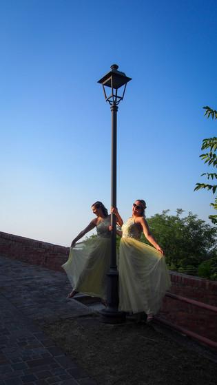 two bridesmaids posing at a lamp post