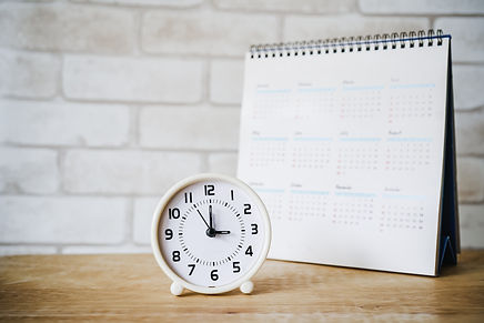 analog clock with blurred calendar  on wooden table.jpg