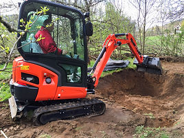 Small excavator with man inside, at work