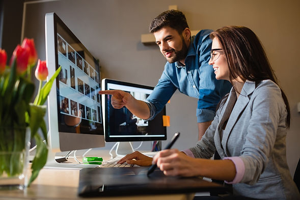 Graphic designer pointing at computer in