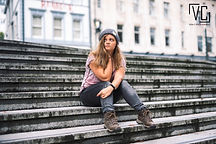 Portrait of a girl sat on some steps in town
