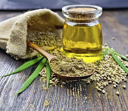 Flour hemp in a wooden spoon, seed in a bag and on the table, oil in a glass jar, on the background of wooden boards