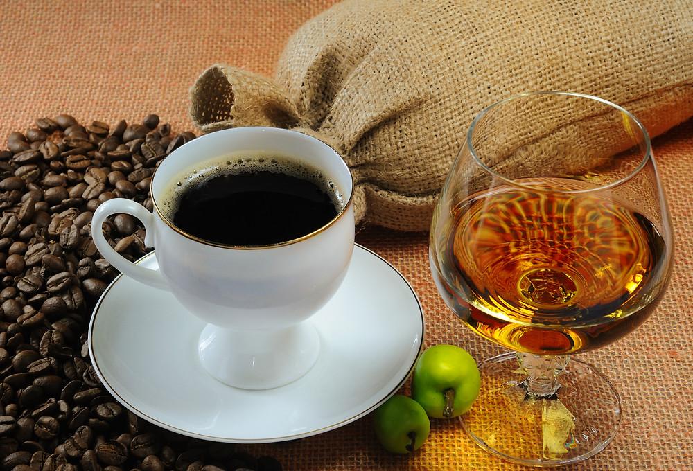 kawa w białej filiżance i kieliszek koniaku