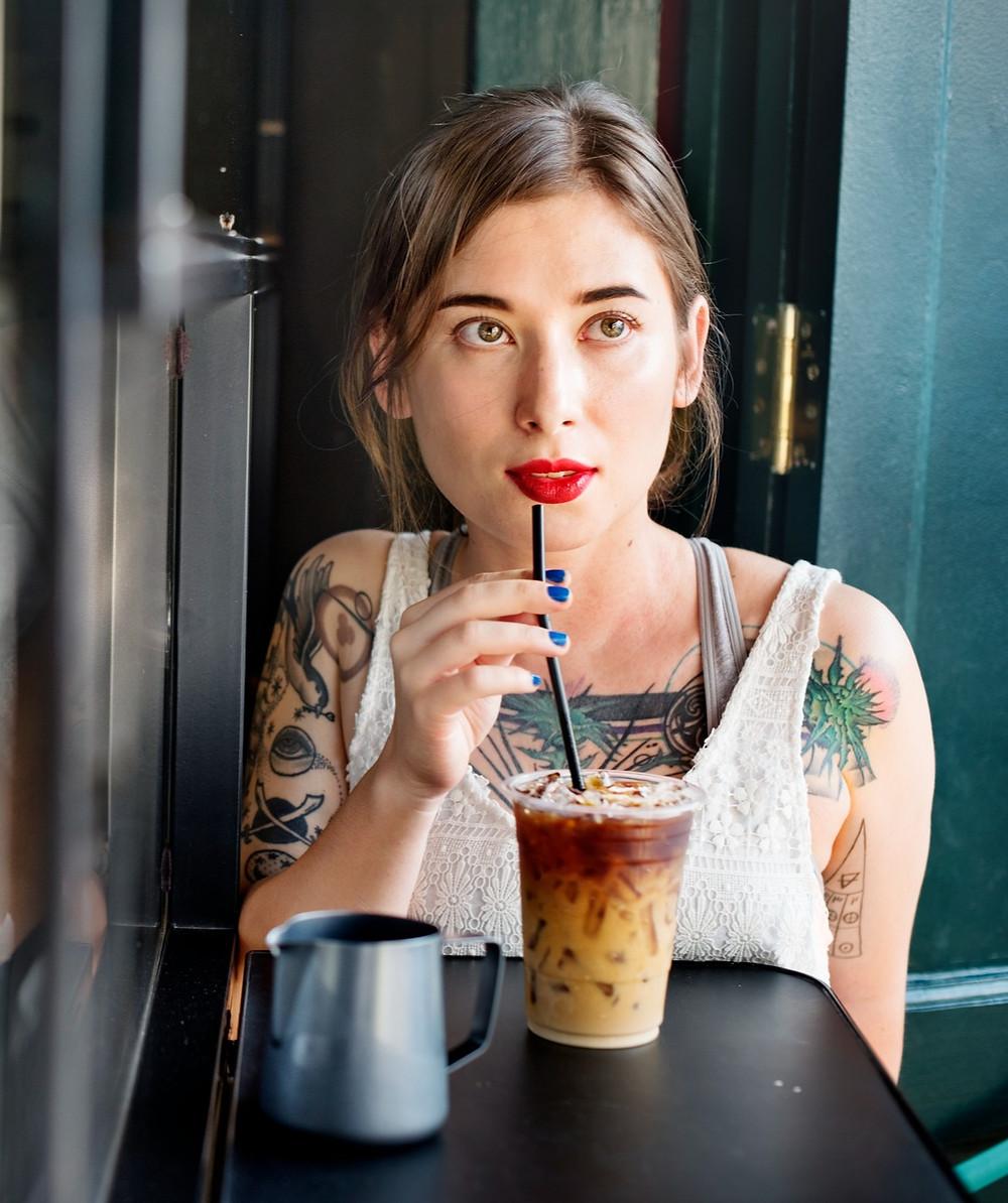 kobieta pije przez słomkę mrożoną kawę