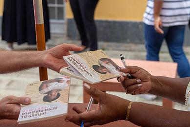 Pessoas trocando livros em lançamento.