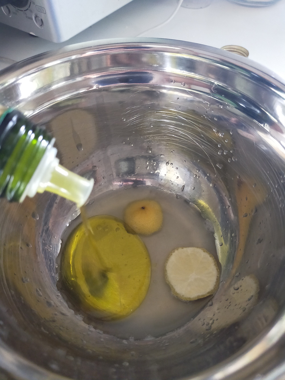 Olive oil is being added to a metal bowl which has the ends of a lemon and lemon juice inside.