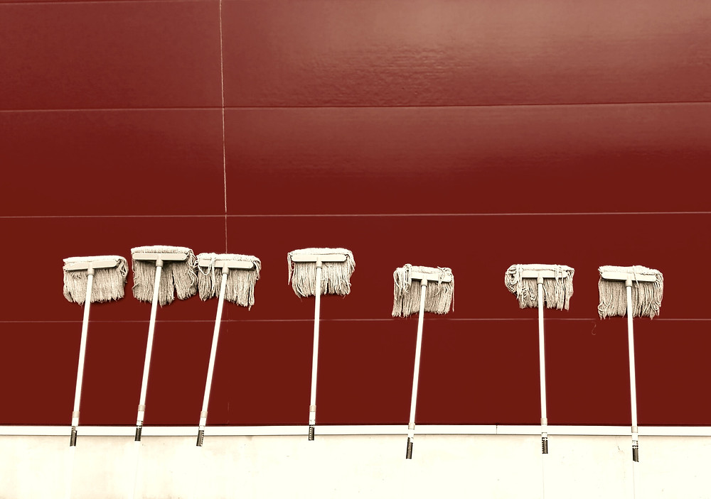 7 old style mop leaning on a burgundy wall