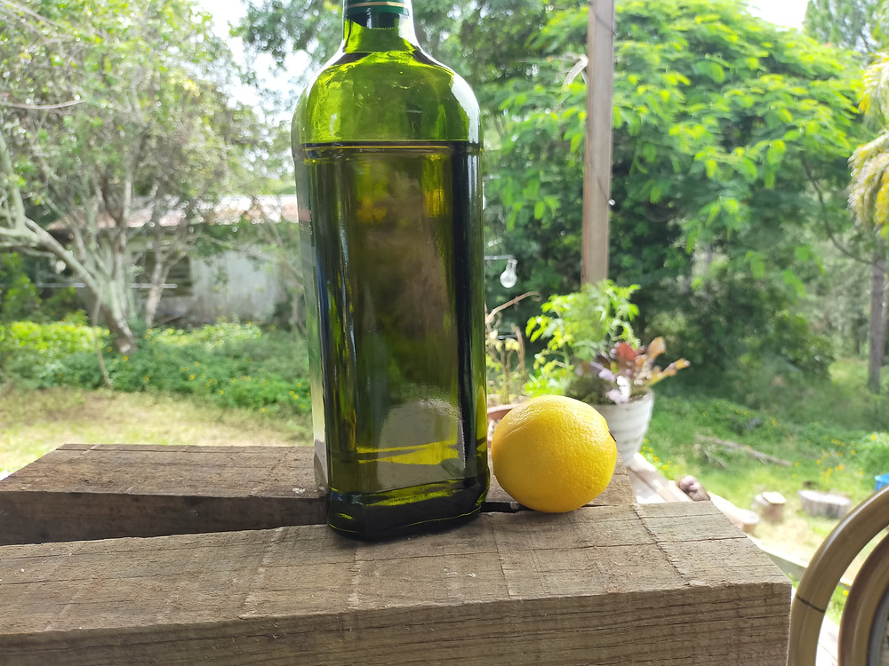A green bottle of olive oil sits on a wooden surface with a whole lemon next to it.