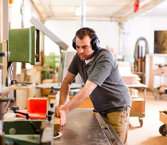 Man with earmuffs sawing wood in workshop
