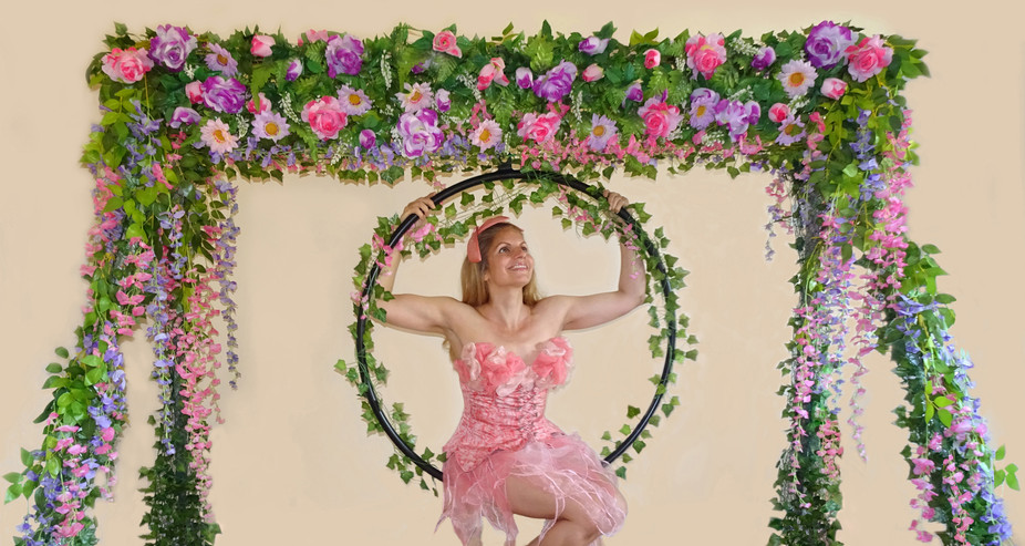 FLORAL THEMED FREESTANDING AERIAL RIG WITH HOOP- dressed with flowers and folige. Ideal for magical, secret or enchanted garden themed events. A striking addition for any wedding or garden party.