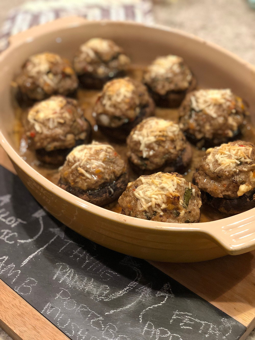 Lamb stuffed mushrooms in yellow le cruset on cutting board with black board and chalk ingredients