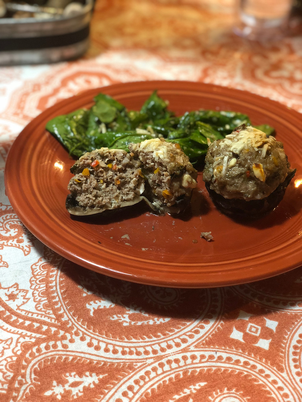 Lamb Stuffed Mushrooms with Simple Spinach Salad on fiesta ware plate