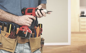 Handman in navy t-shirt and jeans, wearing a tan leather tool belt, holds a red drill