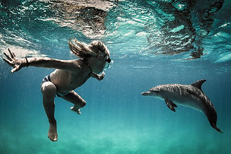 small_boy_child_dive_swim_with_wild_dolp