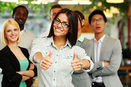 happy-businesswoman-standing-with-thumbs-up-in-front-her-colleagues.jpg