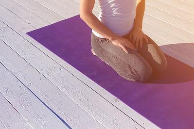 Canva - Woman sitting on purple yoga mat